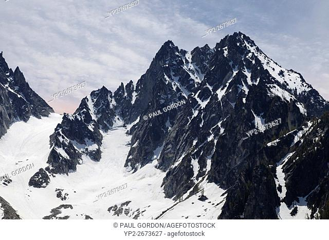 Alpine Lakes Wilderness, Washington: North face of Colchuck Peak in the Stuart Range of the Enchantments. To the left, an orage glow from an circumhorizontal...