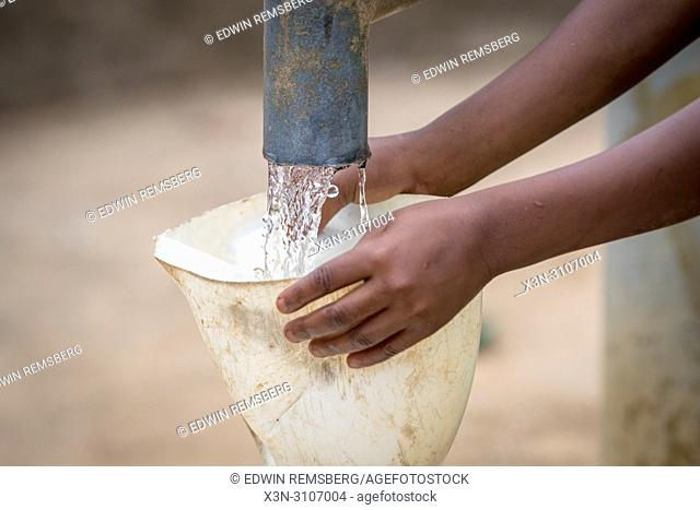 Small hands hold a funnel so that a water jug can be filled from a pump in Ganta, Liberia