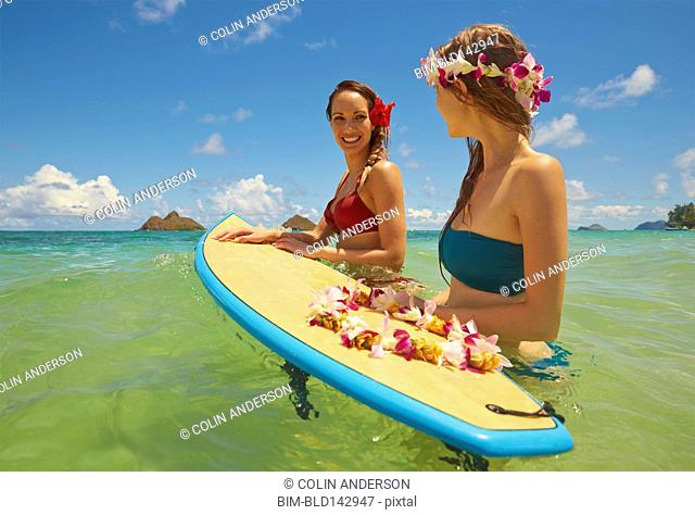 Women floating on surfboard in ocean