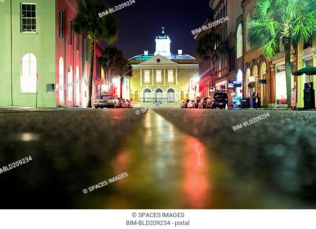 Illuminated buildings along city street at night, Charleston, South Carolina, United States