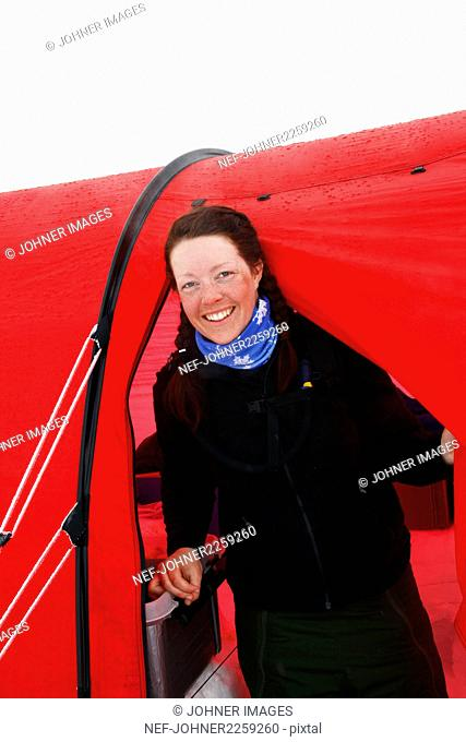 Portrait of smiling woman in front of tent in winter day