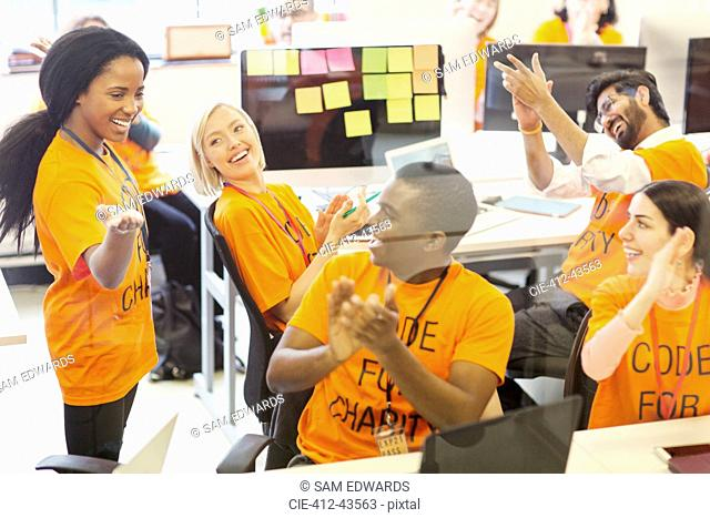 Enthusiastic hackers cheering, coding for charity at hackathon