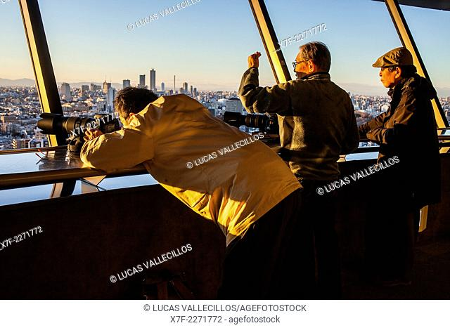 photographers on the top of a skyscraper, shooting photos of the skyline at sunset Tokyo, Japan