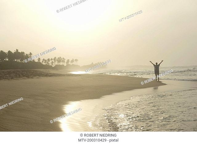 Woman standing with spreading hands on the beach, Tangalle, South Province, Sri Lanka