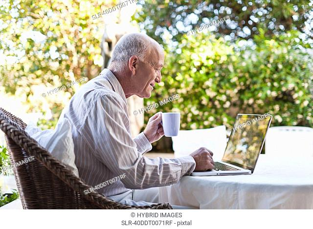 Older man using laptop outdoors