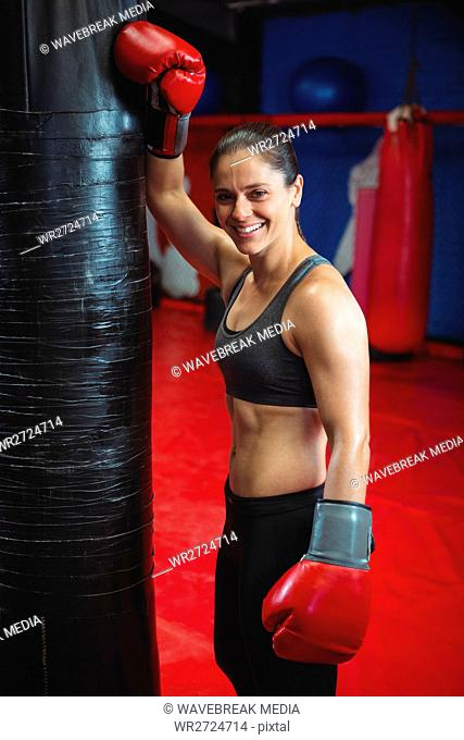 Smiling female boxer standing in fitness studio