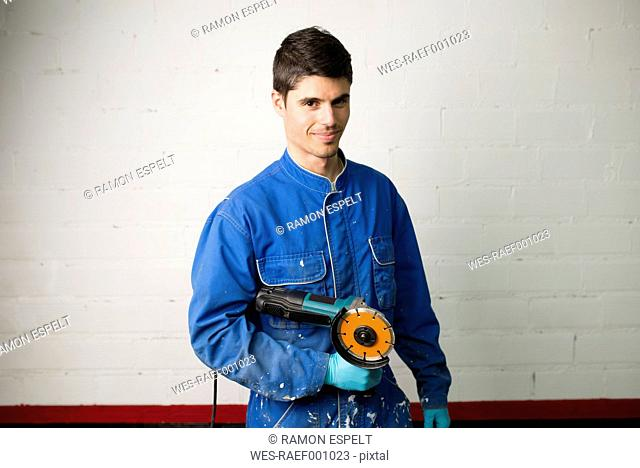 Portrait of a construction worker holding an angle grinder
