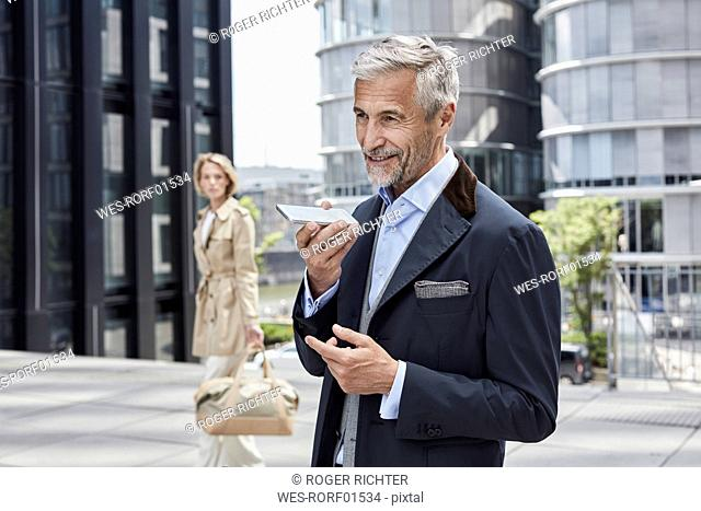 Germany, Duesseldorf, portrait of mature businessman talking on mobile phone