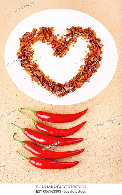 Hot love concept, red chili peppers on plate arranged in heart shape
