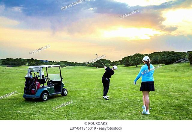 Young couple with cart on the golf fairway at sunset