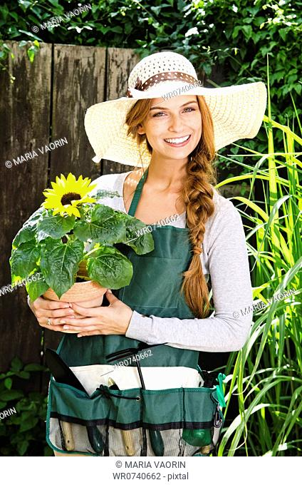 Smiling young woman with sunflower in garden