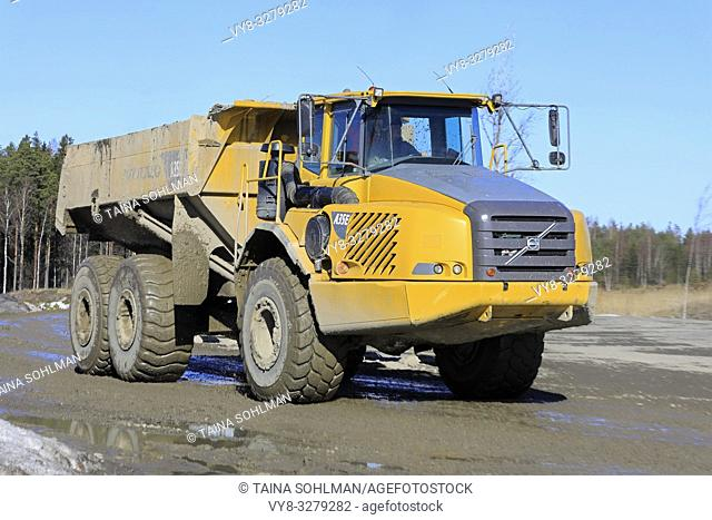 Lieto, Finland - March 22, 2019: Volvo A35E articulated dumper driving at speed along dirt road by a construction site on a sunny day of spring