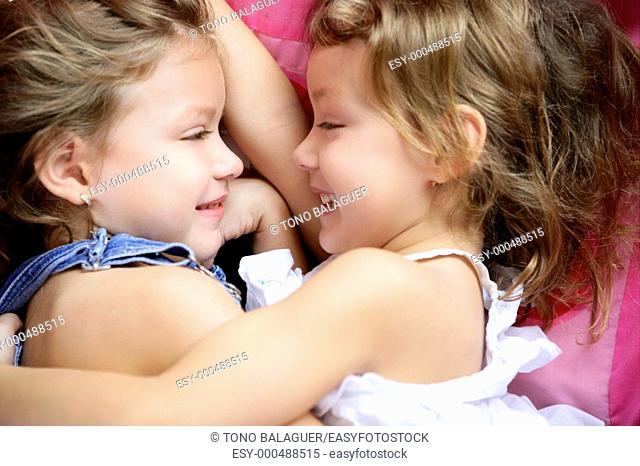 Two twin sisters in a hug, close up portrait over pink
