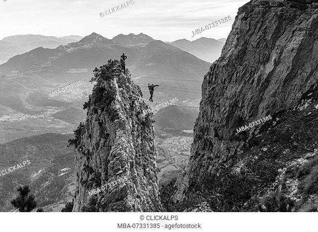 An hiker over a tibetan bridge at via ferrata delle Aquile. Paganella, Trento, Trentino, Italy
