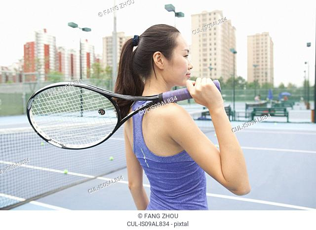 Young female tennis player with tennis racket on shoulder on tennis court