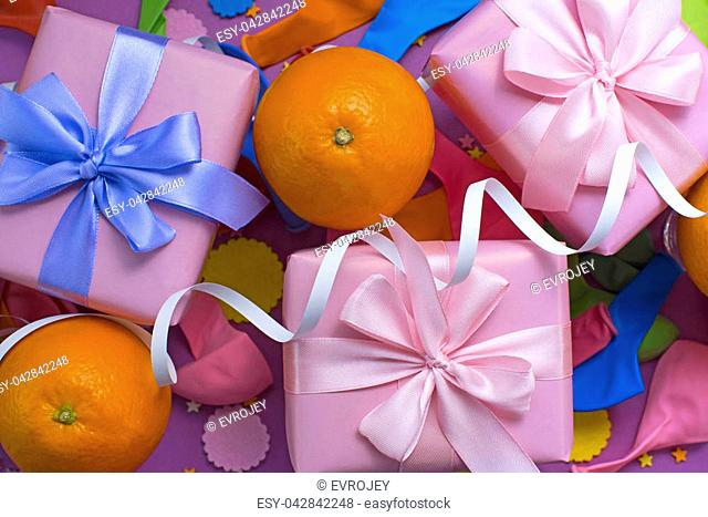 Decorative composition Three boxes with gifts Satin ribbon Bow Oranges Confetti Serpentine birthday party. The view from the top