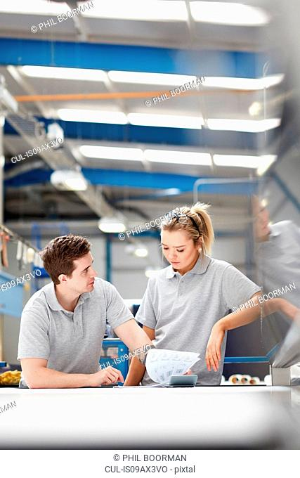 Manager advising female worker on production line in factory