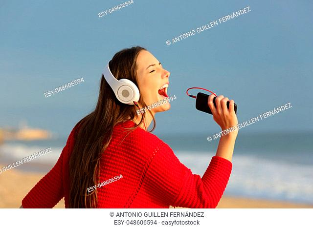 Funny teen singing and listening to music on the beach