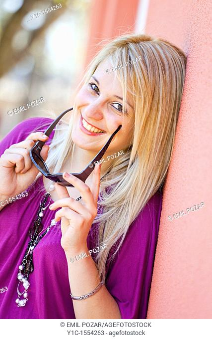 Attractive young woman happy and smiling with sunglasses in hands