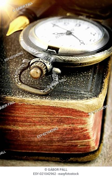 Old book and pocket watch (macro photo)
