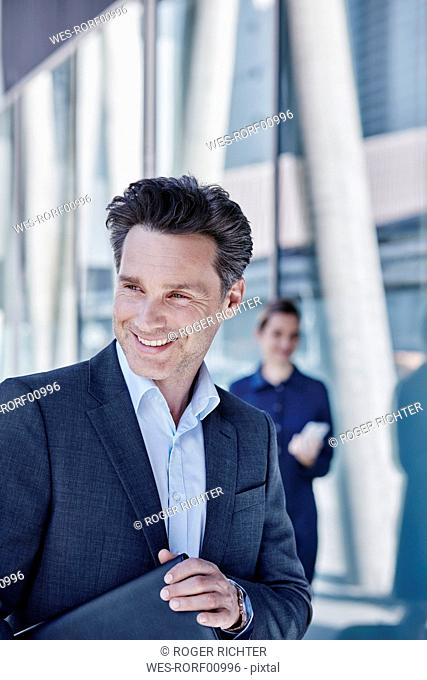 Portrait of smiling businessman with briefcase