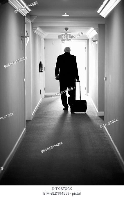 Caucasian businessman pulling luggage in hotel hallway