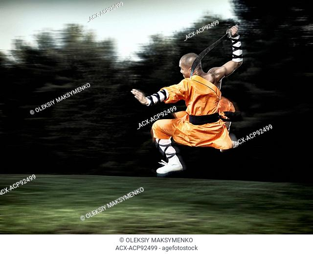 Shaolin warrior monk in mid-air jump with a broad sword