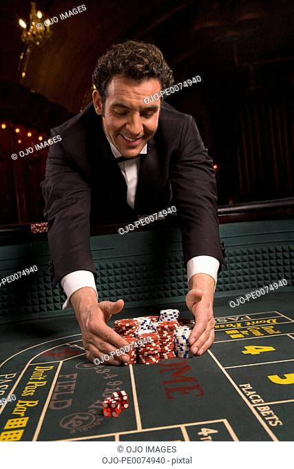 Man gathering poker chips in casino Stock Photos and Images