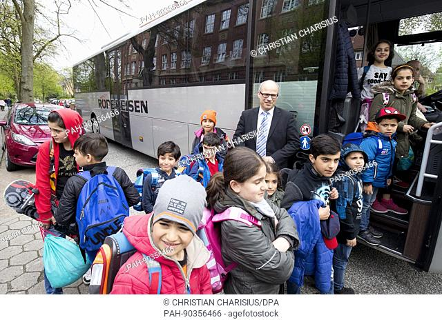 Hamburg's Senator for Education Ties Rabe stands with refugee children next to a bus in front of the all-day primary school Ernst-Henning-Strasse in...