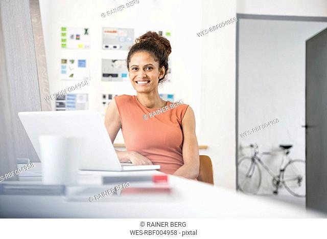 Smiling woman sitting at office desk using laptop