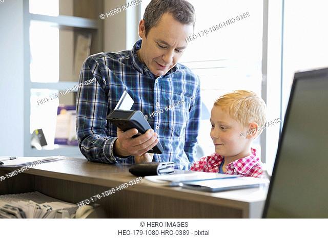 Man using credit card reader at dentists office