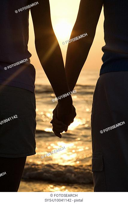 Caucasian mid-adult mother and teenage daughter standing on beach at sunset holding hands