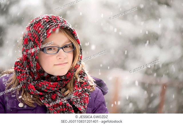 Girl (10-12) standing in snow and looking at camera