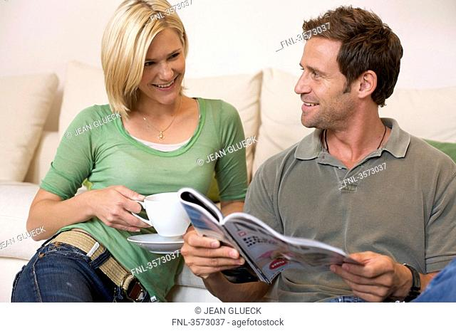 Relaxed couple at home with magazine and coffee