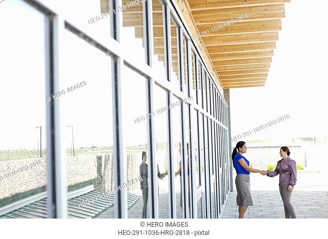 Businesswomen shaking hands outside office building