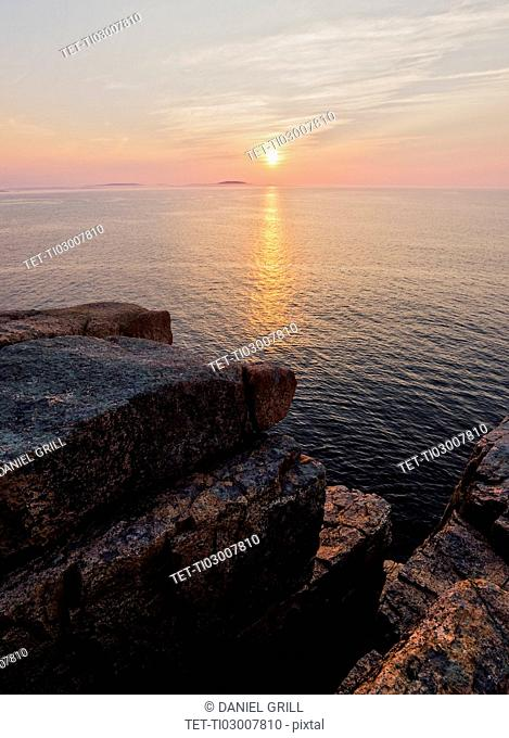 Rocky cliff by sea at sunrise