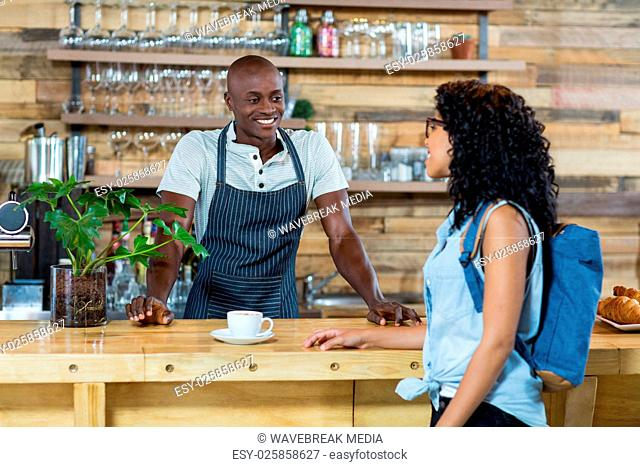Woman interacting with waiter at counter