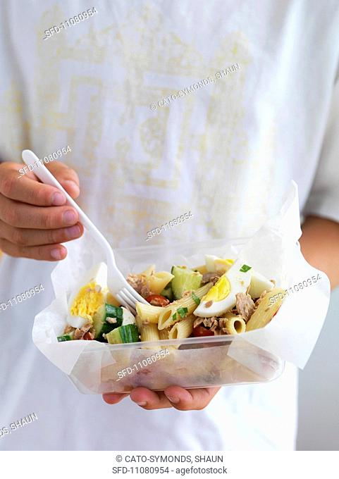 A person holding a lunch box with tuna-pasta salad