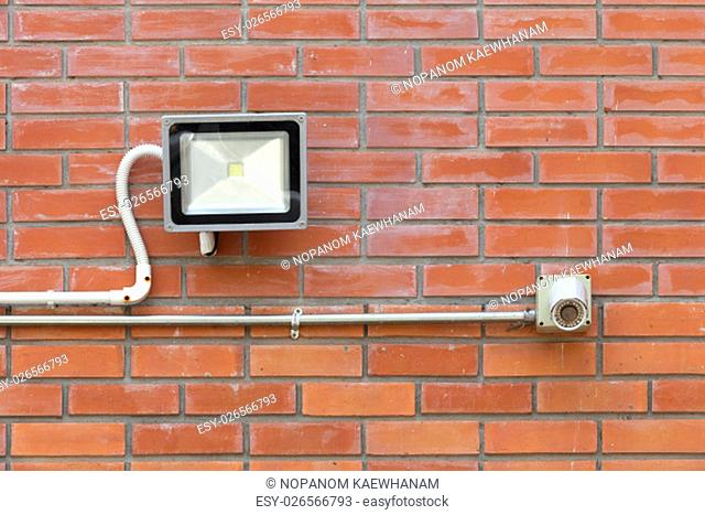 spotlight lamp and CCTV on red brick tile wall background texture, security, watching