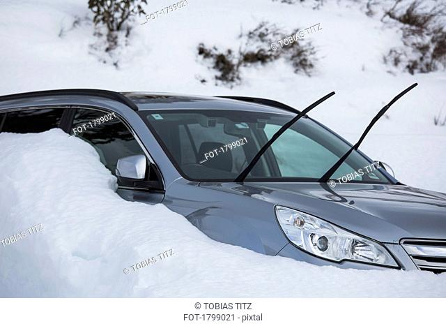Car parked in snow with windshield wipers up