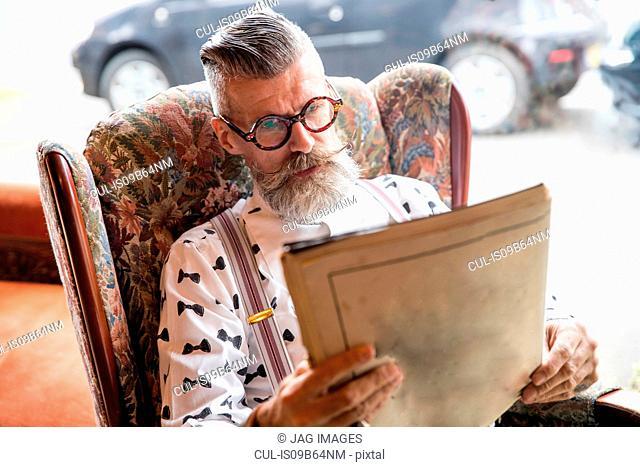 Quirky vintage senior man reading vintage magazine in tea rooms
