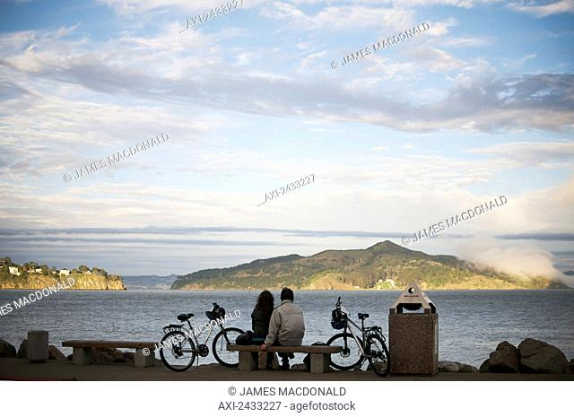 A couple sits by San Francisco Bay as the sun sets; San Francisco, California, United States of America