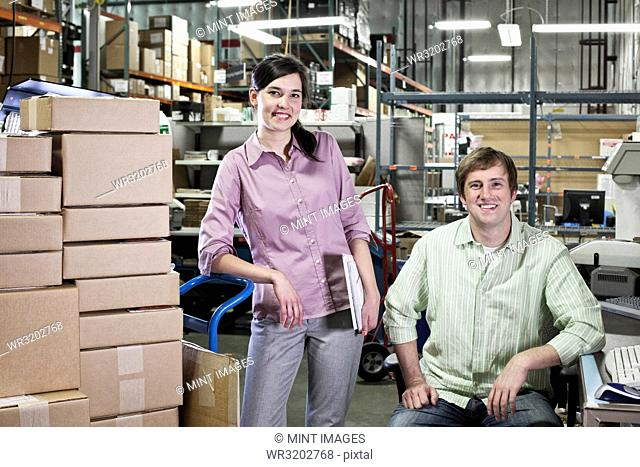 A portrait of a team of two Caucasian male and female workers in a parts department work site