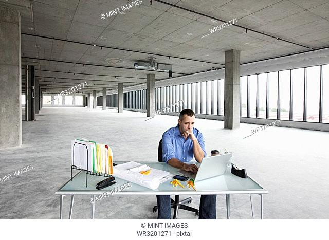 A Caucasian male business owner at his temporary desk in a new raw business space