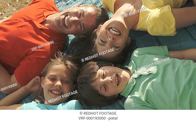 Overhead view of family with lying on rug in countryside