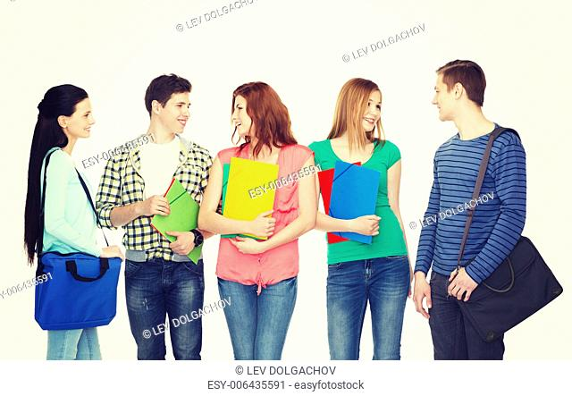 education and people concept - group of smiling students with bags and folders having discussion
