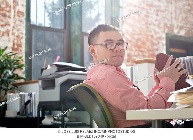 Hispanic businessman holding football at office desk