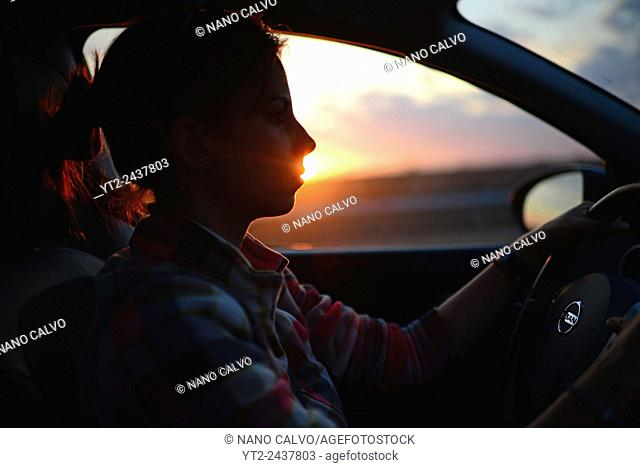 Young woman driving car at sunset