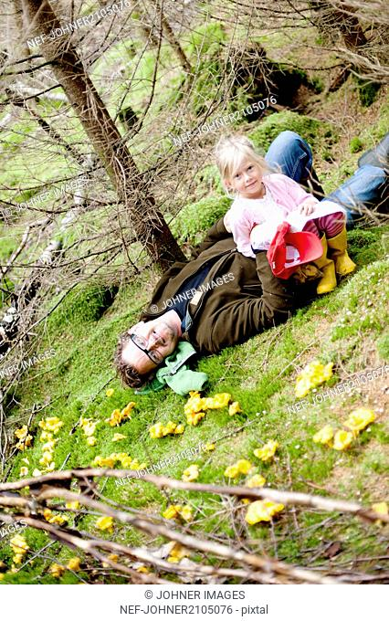 Girl with father on moss in forest