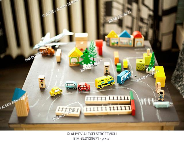 Wooden buildings and car toys on table